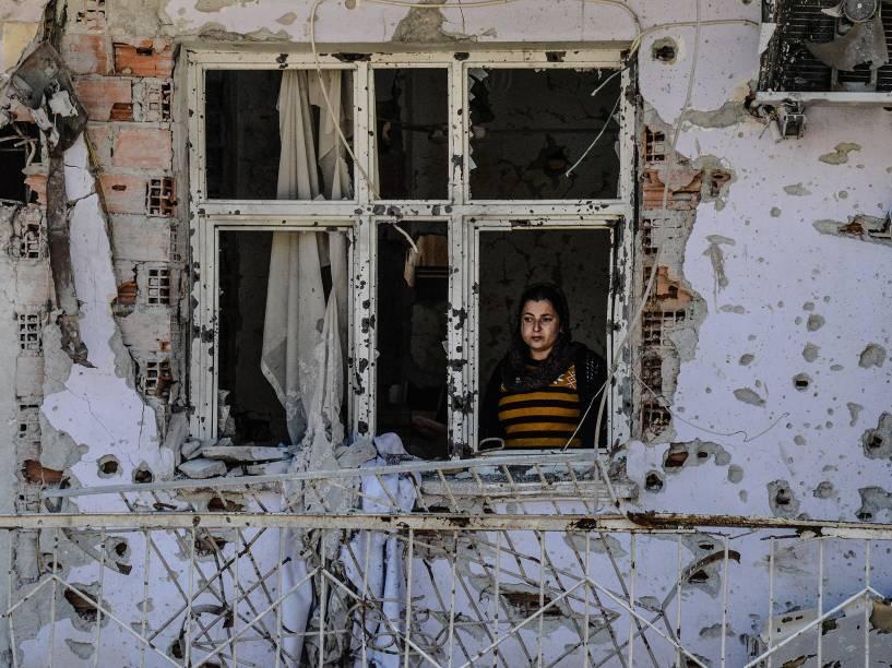 Mulher olha através de uma janela de sua casa em ruínas nesta terça-feira (08), no Dia Internacional da Mulher em Cizre, na Turquia