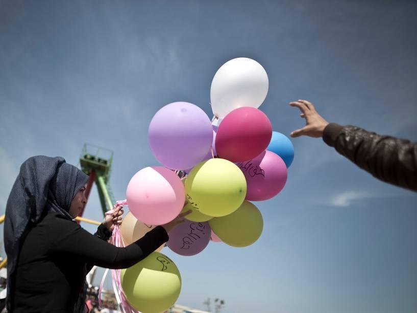 """Uma mulher palestina segura balões com frases sobre """"direitos das mulheres"""" para comemorar o Dia Internacional da Mulher, nesta terça-feira (08), em um parque na Cidade de Gaza"""