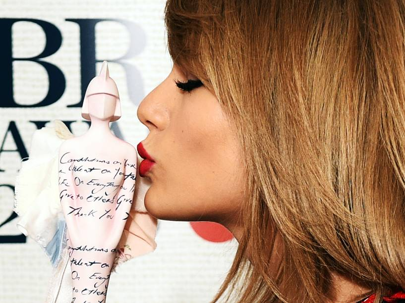 Taylor Swift beija a estatueta de Melhor Artista Internacional Feminina Solo durante o Brit Awards 2015