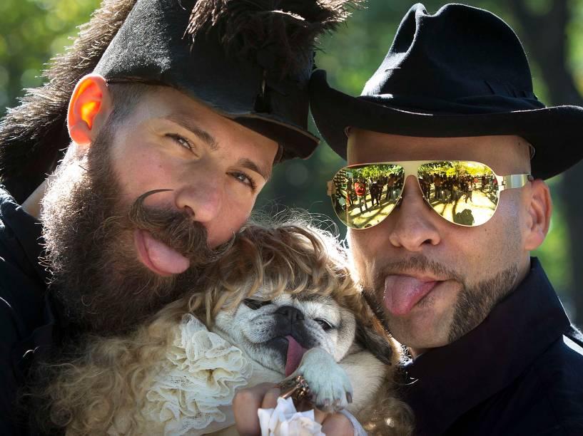 Homens posam com cachorro duranteo desfile anual de Halloweenda Tompkins Square, em Nova York, EUA