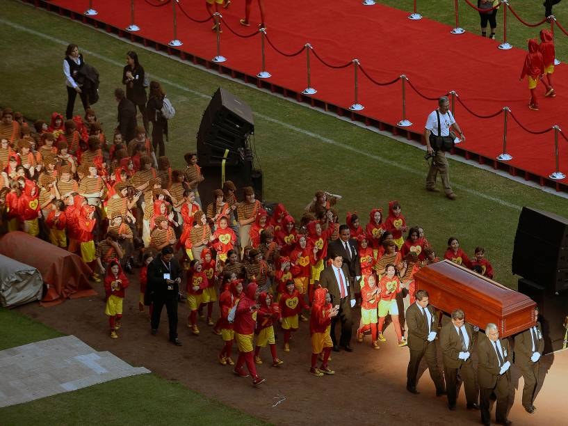 Corpo de Roberto Bolaños deixa o estádio Azteca seguido por crianças vestidas dos personagens Chapolin Colorado e Chaves - 30/11/2014