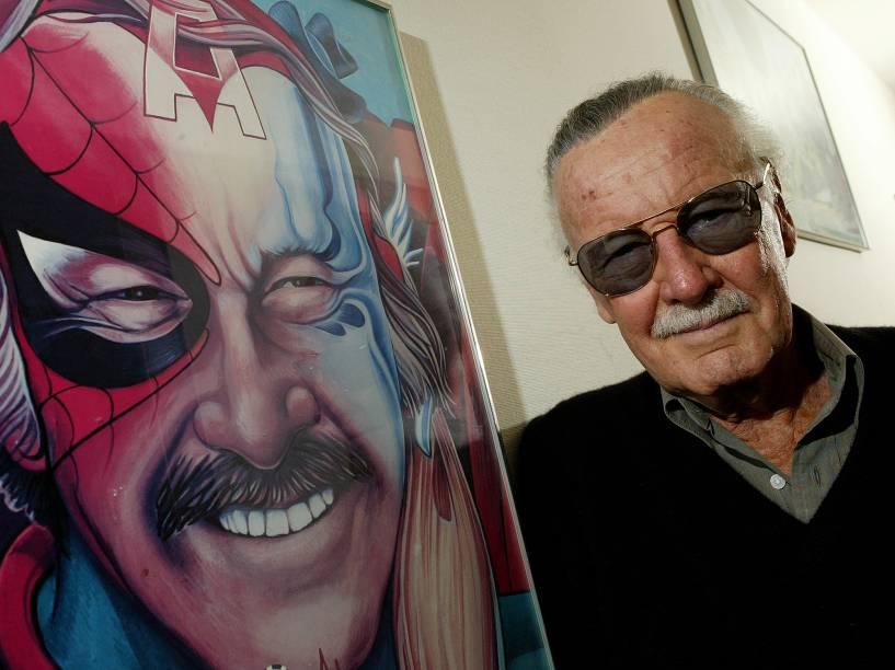 Stan Lee posa em seu escritório, em Beverly Hills, na California, ao lado de um quadro que o representa junto com algumas das personagens criadas ao longo de sua carreira, em 2004