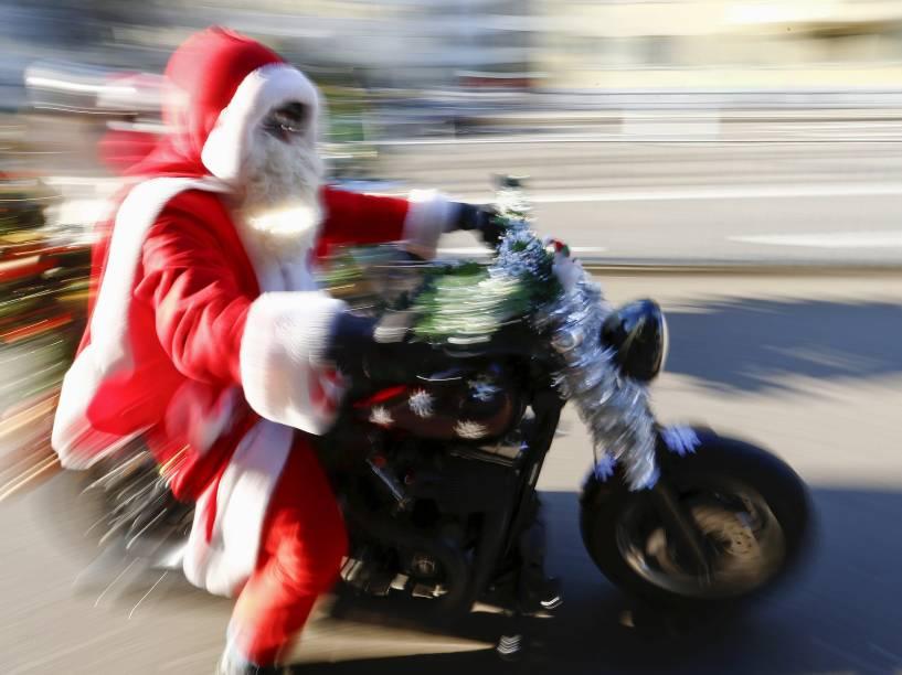 Homem vestido de papai noel pilota uma Harley Davidson durante evento de caridade em Zurique, na Suíça
