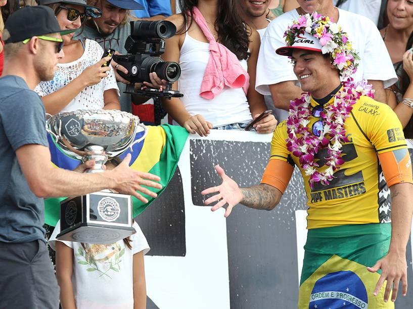 Gabriel Medina recebe o troféu do surfista Mick Fanning e comemora o título do Circuito Mundial de Surfe (WCT), no Billabong Pipe Masters, praia de Pipeline, Ilha de Oahu, no Havaí