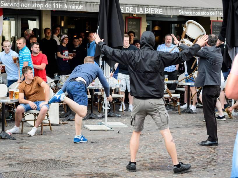 Homem joga uma cadeira enquanto um grupo de torcedores russos provocam um grupo de torcedores ingleses no centro de Lille, na França - 14/06/2016