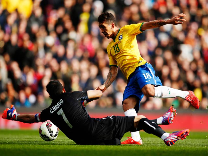 O atacante Roberto Firmino dribla o goleiro Claudio Bravo para marcar o gol da vitória sobre o Chile
