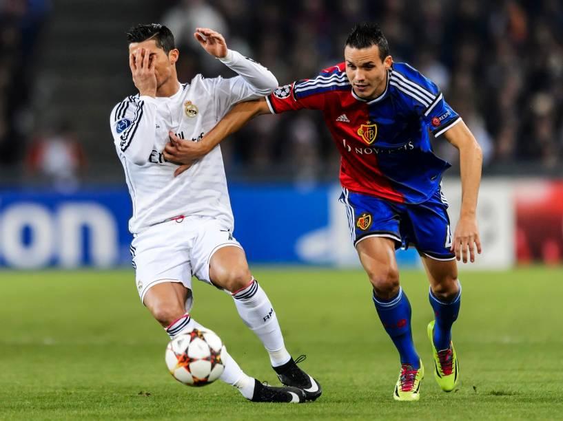 Lance entre Cristiano Ronaldo, do Real Madrid, ePhilipp Degen, do Basel,durante a partida disputada pela Liga dos Campeões
