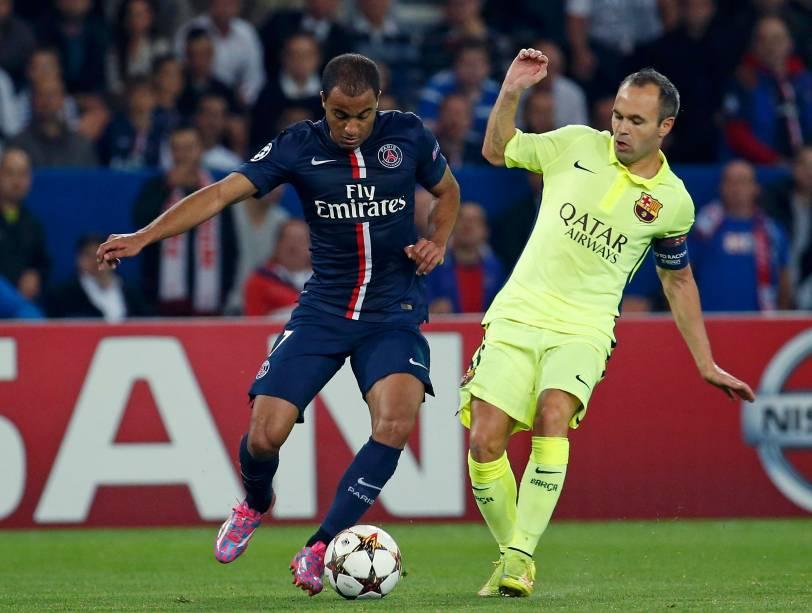Lucas (PSG) e Inisesta (Barcelona) disputam bola durante jogo pela Liga dos Campeões