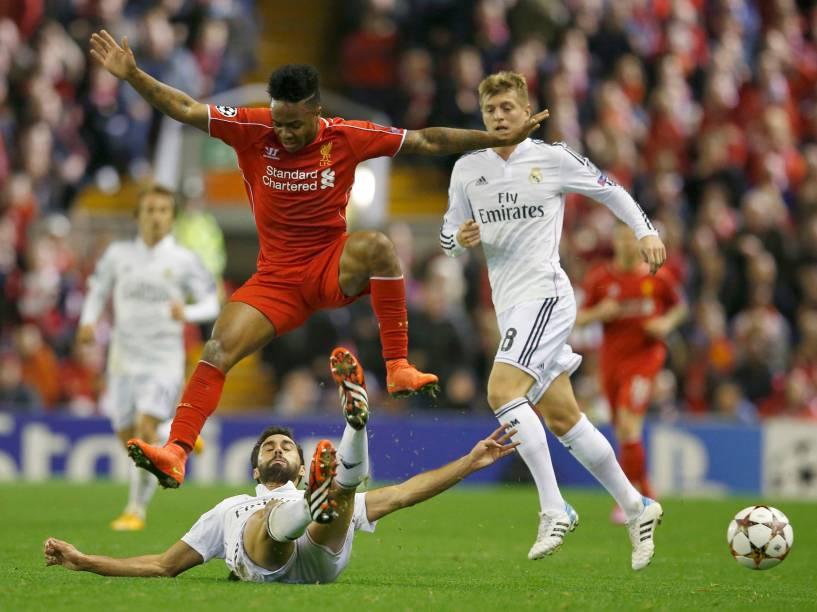 Raheem Sterling, do Liverpoo, pula durante disputa de bola com Arbeloa, do Real Madrid, pela Liga dos Campeões na Inglaterra