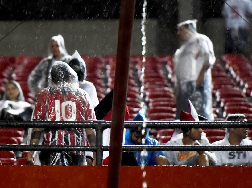 Torcida do São Paulo tenta se proteger da chuva na partida contra Danúbio do Uruguai, pela Libertadores - 25/02/2015