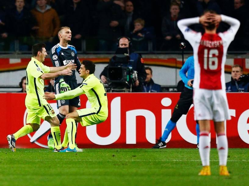 Ao fundo, jogadores do Barcelona, Messi e Bartra, comemoram gol que abriu o placar do jogo do Barcelona contra o Ajax, pela Liga dos Campeões