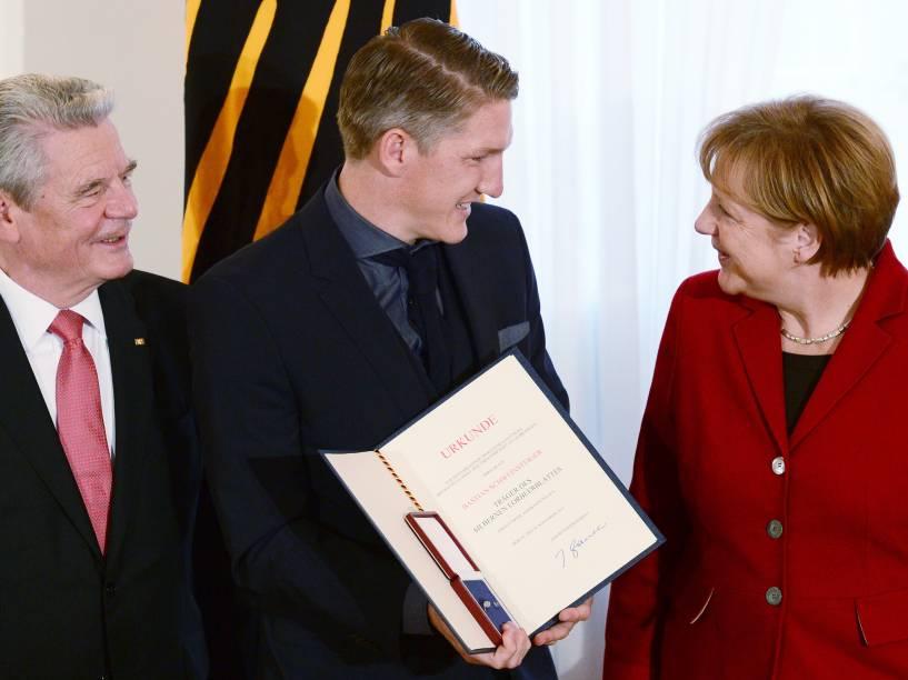 Bastian Schweinsteiger posa com o presidente Joachim Gauck (à esq.) e a chancelerAngela Merkel