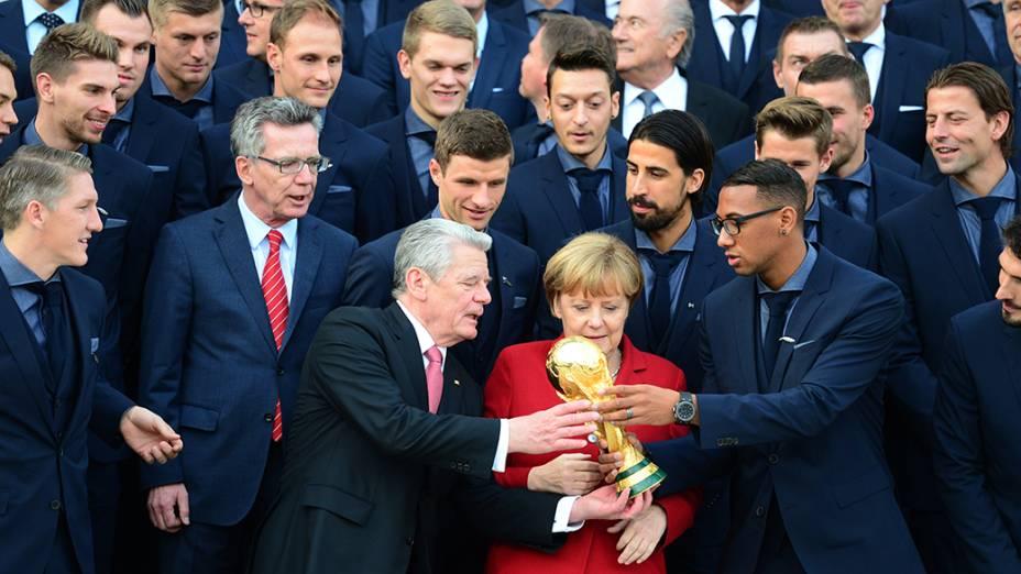 Jogadores da seleção alemã de fuebol posam com a taça da Copa do Mundo após receberem das mãos do presidente Joachim Gauck (à esq.) e da chanceler Angela Merkel uma condecoração no Palácio Presidencial de Bellevue, em Berlim