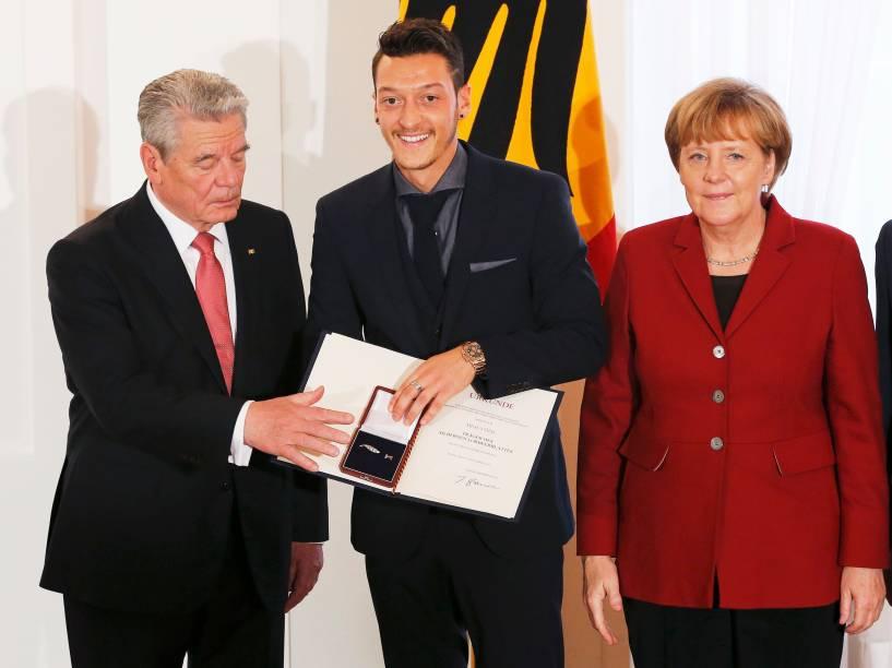 Mesut Özil posa com o presidente Joachim Gauck (à esq.) e a chanceler Angela Merkel