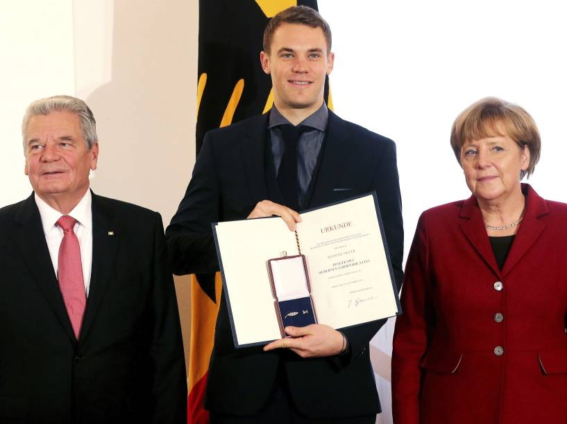 Goleiro Manuel Neuer posa com o presidente Joachim Gauck (à esq.) e a chanceler Angela Merkel depois de receber a condecoração Laurel de Prata, o principal prêmio da Alemanha para o sucesso desportivo, no Palácio Presidencial Schloss Bellevue, em Berlim
