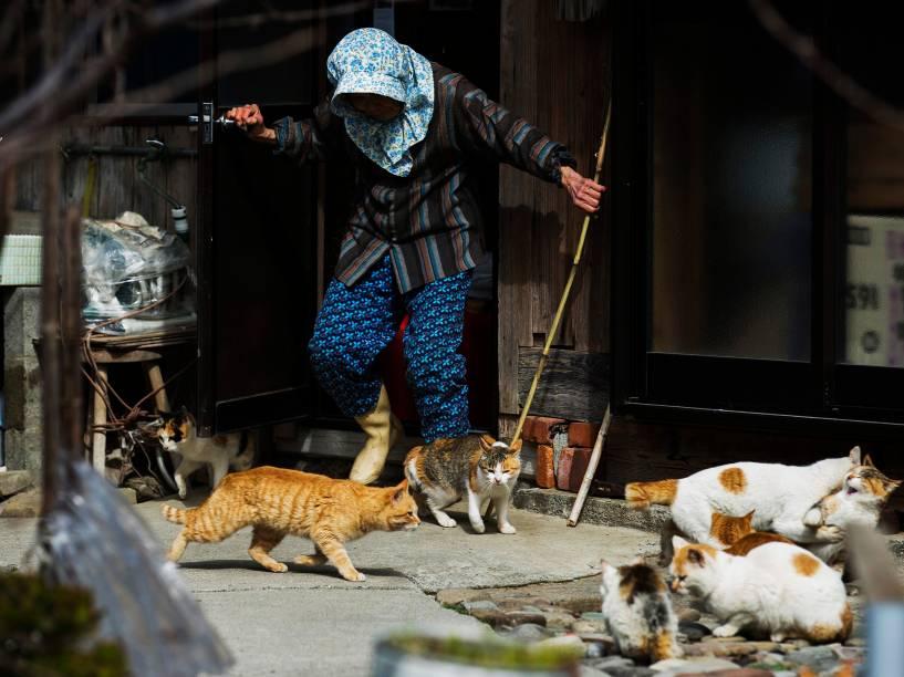 """Mulher tenta espantar os gatos de sua casa na ilha de Aoshima, sul do Japão conhecida como a """"Ilha dos Gatos"""""""