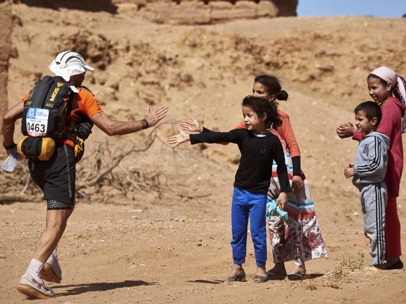 Competidor é saudado por crianças, durante a Maratona das Areias, realizada no sul do Deserto do Saara, no Marrocos