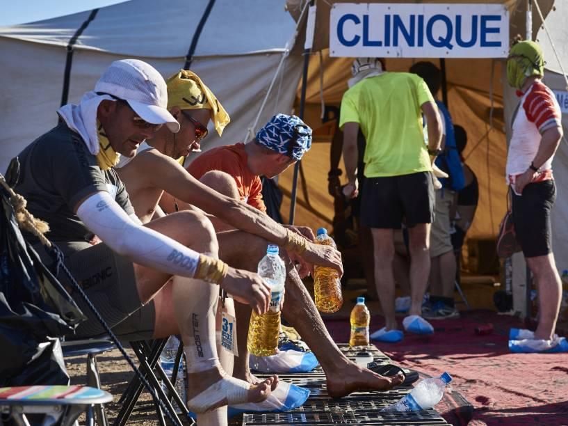 Competidores recebem tratamento para os pés, durante a segunda etapa da 31ª edição da Maratona das Areias, no sul do deserto do Saara, em Marrocos