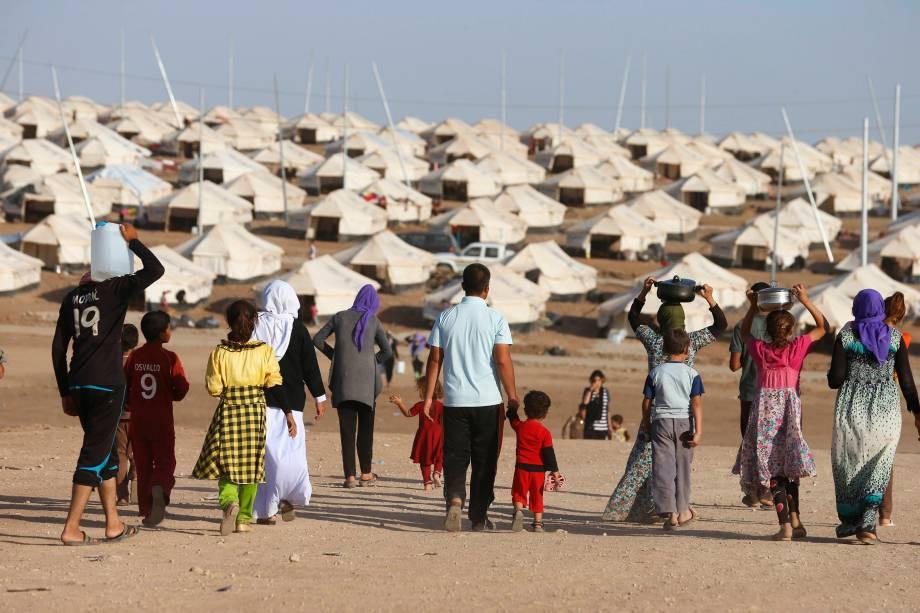 Cidadãos da minoria Yazidi, que fugiram da violência na cidade iraquiana de Sinjar, andam porBajed Kadal, um campo de refugiados no sudoeste da província de Dohuk, extremo nortedo país