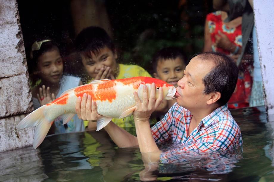 Dono de um zoológico de Malabon, Manny Tangco, beija uma carpa japonesa Koi enquanto crianças observam a apresentação da nova atração do local, chamada de O mundo das Kois, no norte da região metropolitana de Manila, nas Filipinas