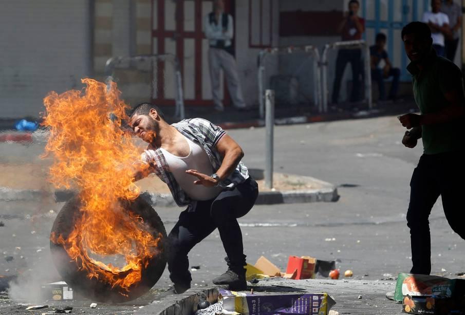 Homem tenta empurrar um pneu em chamas durante protesto em Hebron, na Cisjordânia, contra a ofensiva israelense em Gaza