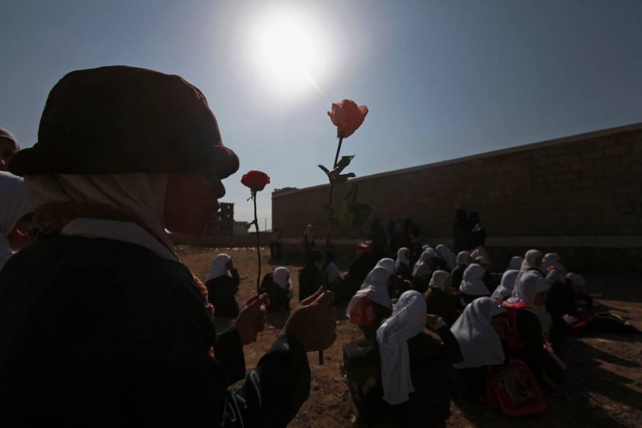 Em frente à escola que foi tomada por rebeldes Xiitas em Sanaa, Yemen, estudante carrega flor simbolizando seu não envolvimento com a guerra