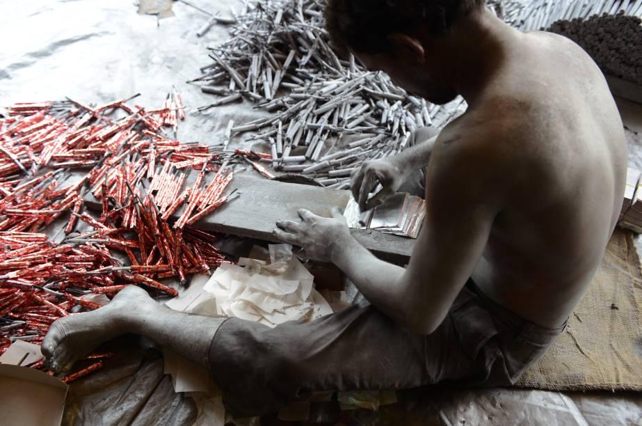 Indiano trabalhador prepara fogos de artifício para festival Hindu, em Ahmedabad, Índia