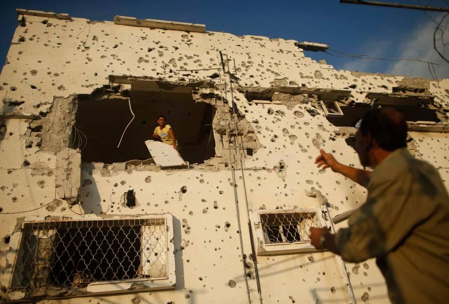Palestino remove seus pertences de sua casa que foi detonada, segundo testemunhas, durante a ofensiva contra Gaza