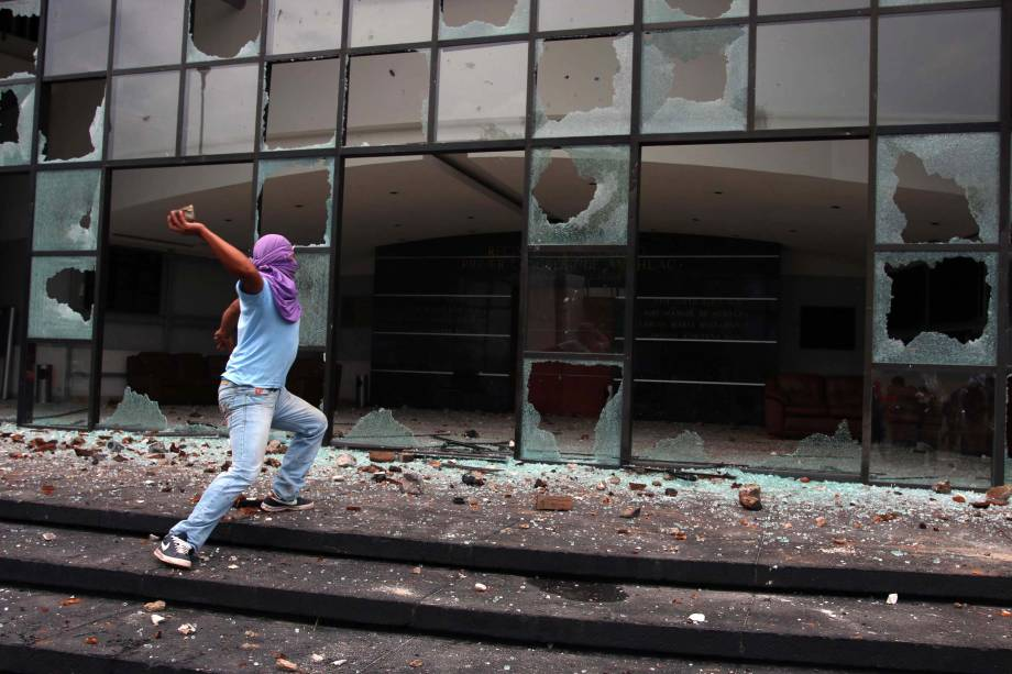 Um jóvem encapuzado joga pedras em frente ao Congresso do Estado de Guerrero durante protesto, no México