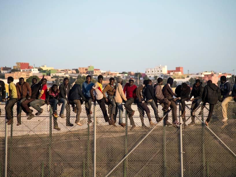 Na imagem,imigrantes são vistos sobre uma cerca nafronteira que separa Marrocos do enclave espanhol de Melilla, na regiãonorte da África.Segundo informações do governo local, ofluxo de imigrantes ilegais lutando para chegar à Espanhajá passado dobrodo registrado no ano passado