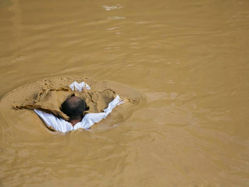 Peregrino cristão mergulha às margens do rio Jordão, nalinha fronteiriça próxima aCisjordânia
