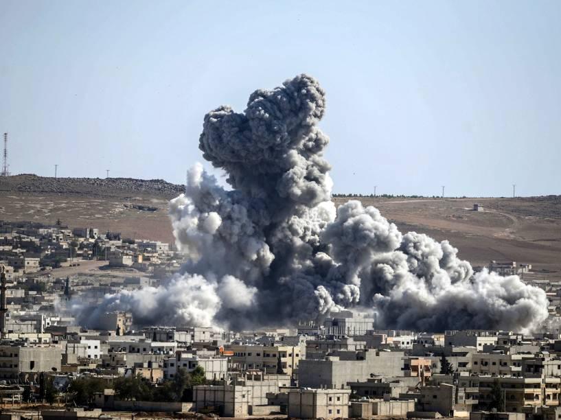 Coluna de fumaça é vista apósexplosão na cidadede Kobane, também conhecido como Ain al-Arab, na Síria. O governo americano, aliado a várias potências mundiais, tem realizado uma série de ataques aéreos em um tentativa de combater o avanço de militantes do Estado Islâmico (EI) por todo o território