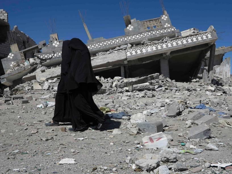 Mulheres vestindo burcas passam em frente a casa de Ali Bedair, líder do partido muçulmano sunita Islah, bombardeada por rebeldes xiitas em Yareem, cidade da província central doIêmen. Combatentes Houthi entraram em confronto com simpatizantes do partido Islahno início desta semana,levantando o especto de um confronto sectário mais amplo no país, que fazfronteira com o maior exportador de petróleo do mundo, a Arábia Saudita