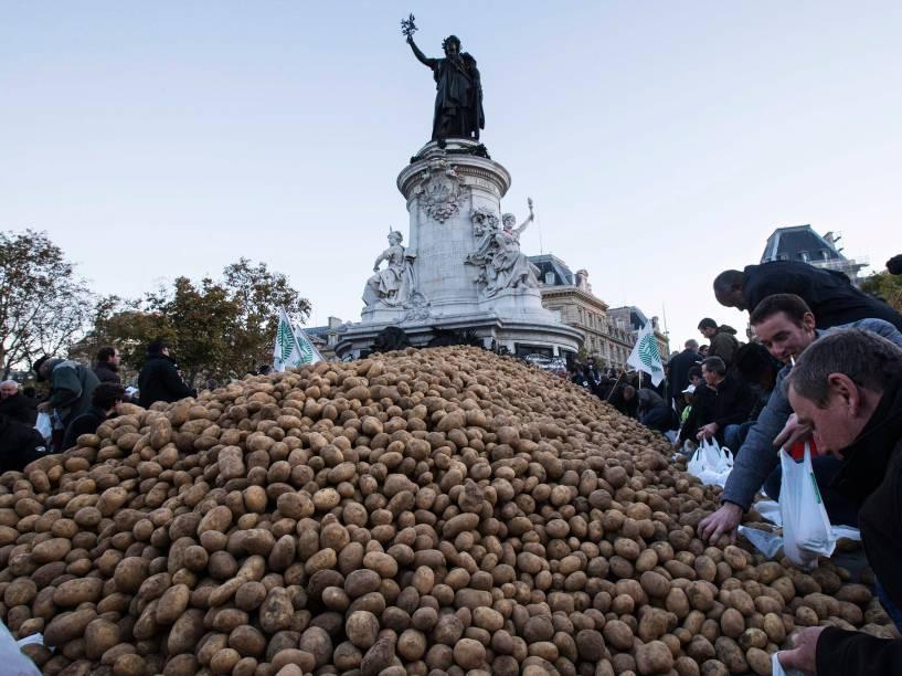 Agricultores colocaram batatas em sacos antes da distribuição na Praça Republique, no centro de Paris. Sindicatos dos agricultores franceses organizaram um dia nacional de protesto contra as restrições e encargos crescentes e a queda dos preços de cereais, leite e vegetais, causada em parte pelas sanções sobre a Rússia - 05/11/2014