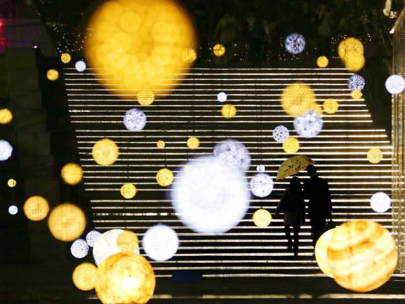 Casal caminha por um centro comercial iluminado com luzes de Natal em Tóquio, no Japão - 06/11/2014