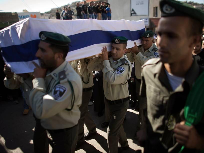 Oficiais israelenses da Polícia de Fronteiras carregam um caixão coberto com a bandeira nacional, durante funeral de um guarda, na região da Galiléia, em Israel