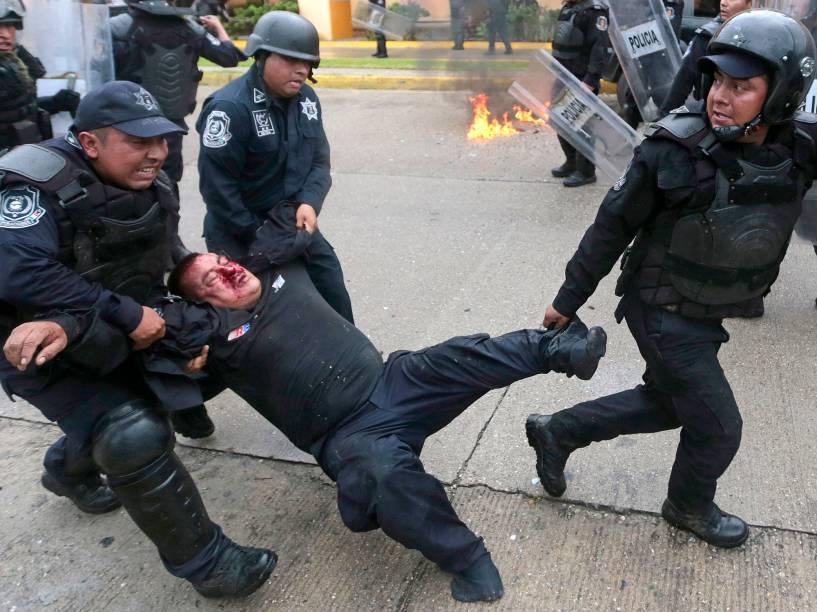 Policial ferido é resgatado durante confrontos com manifestantes em um protesto provocado pelo massacre de 43 estudantes mexicanos, nas proximidades do aeroporto de Acapulco