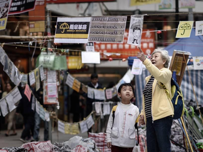 Idosa explica a uma criança o significado dos cartazes criados por manifestantes pró-democracia em um local de protesto em um distrito da Baía de Causeway, em Hong Kong - 14/11/2014