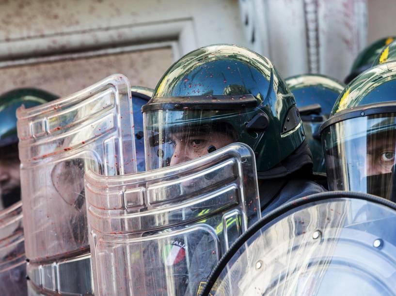 Agentes da polícia italiana, se protegem do ataque de manisfestantes que jogam ovos e fogos de artifício durante um protesto em frente ao edifício do Ministério da Economia, em Roma - 14/11/2014