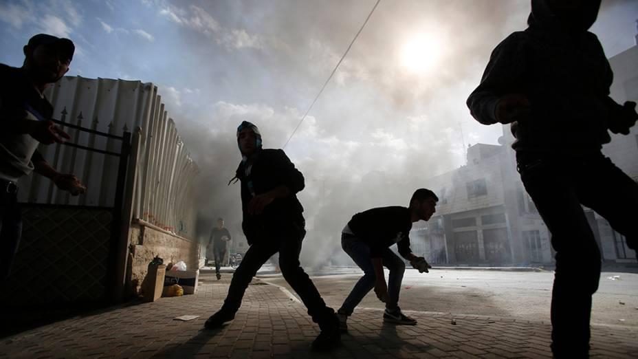 Manifestantes palestinos se preparam para atirar pedras em soldados do Exército israelense durante confrontos na cidade de Hebron - 14/11/2014