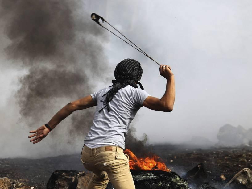 Manifestante palestino usa seu estilingue para atirar uma bomba de gás lacrimogêneo disparada por soldados israelenses durante confrontos nos arredores do assentamento judaico de Kedumim, perto da cidade de Nablus, na Cisjordânia - 14/11/2014