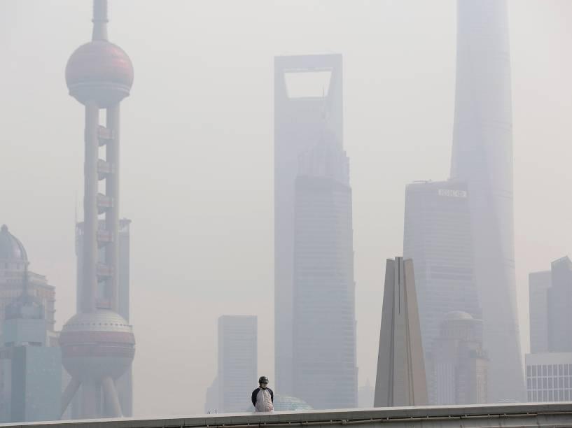 Homem usa uma máscara para se proteger da poluição, em uma ponte em frente ao distrito financeiro de Pudong, em Xangai, na China