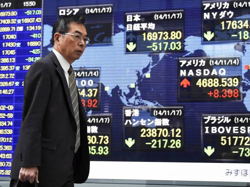 Pedestre passa por uma tela mostrando índices do mercado de ações de diferentes países, em Tóquio. O Japão entrou em recessão técnica após uma contração do PIB no trimestre de julho a setembro, segundo dados oficiais