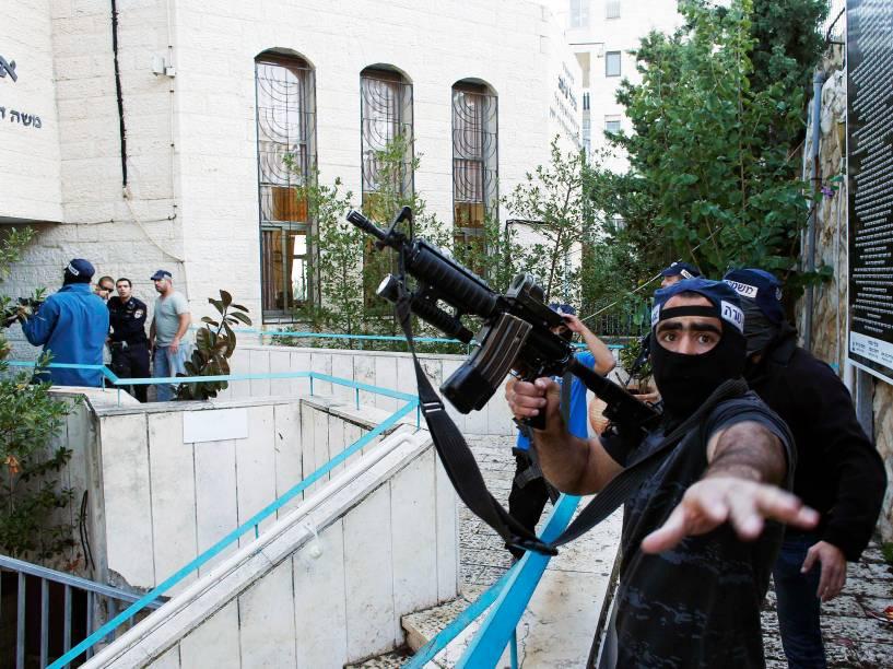 Policial israelense segura uma arma perto da cena de um ataque em que dois suspeitos palestinos armados com machados e facas mataram quatro pessoas em uma sinagoga de Jerusalém