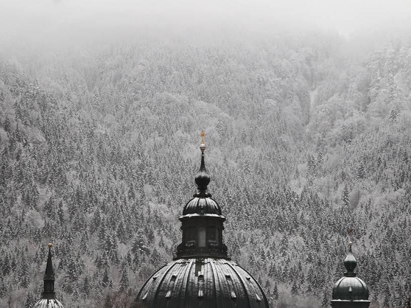 Torre da abadia de Ettal fotografada à frente da paisagem coberta por neve, em Ettal, sul da Alemanha