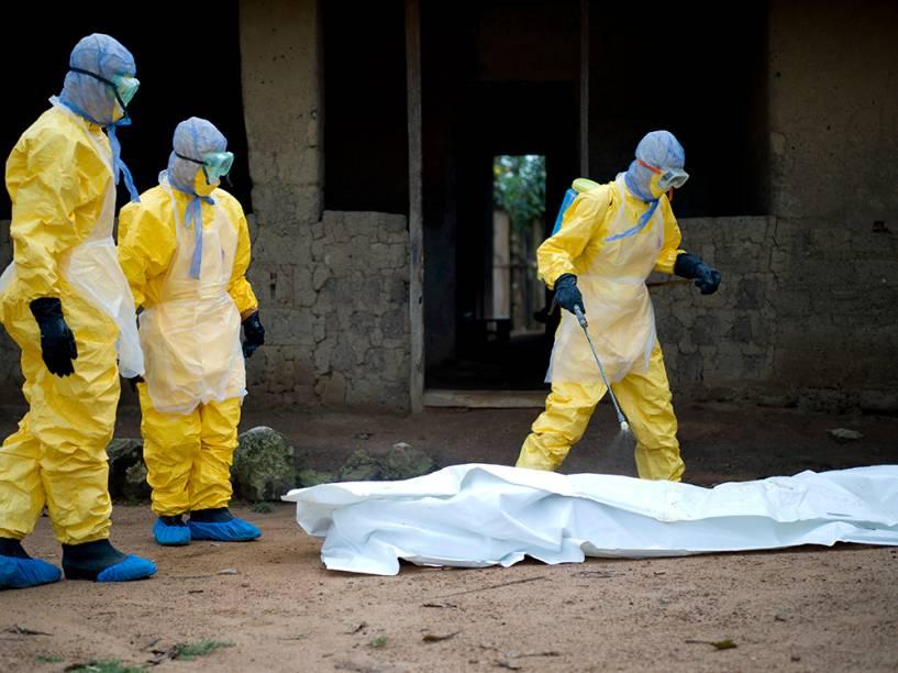 Profissionais de saúde da Cruz Vermelha da Guiné retiram o corpo de uma vítima do vírus Ebola, em Momo Kanedou. Guiné, Libéria e Serra Leoa, foram os mais atingidos pelo epidemia que já matou mais de 5 mil pessoas este ano, segundo a OMS