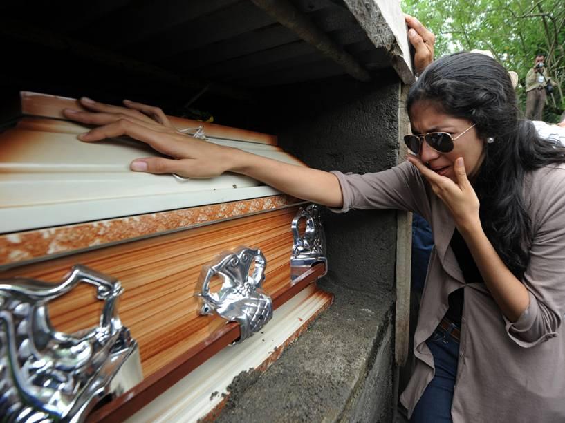 Mulher chora ao lado do caixão da ex-Miss Honduras, Maria José Alvarado, assassinada junto com a irmã Sofia Trinidad Alvarado, na cidade de Santa Bárbara