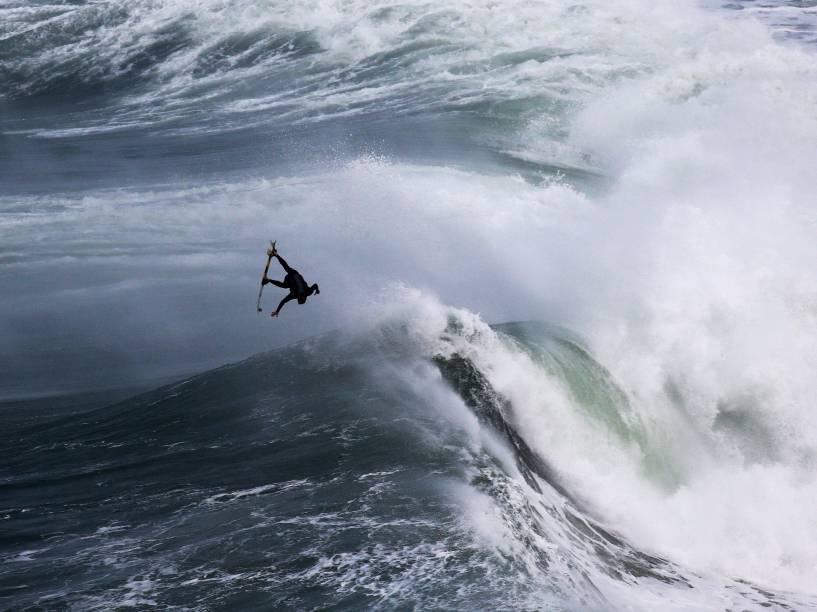 Surfista vai ao ar após pegar uma onda gigante na Praia do Norte, em Nazaré, Portugal
