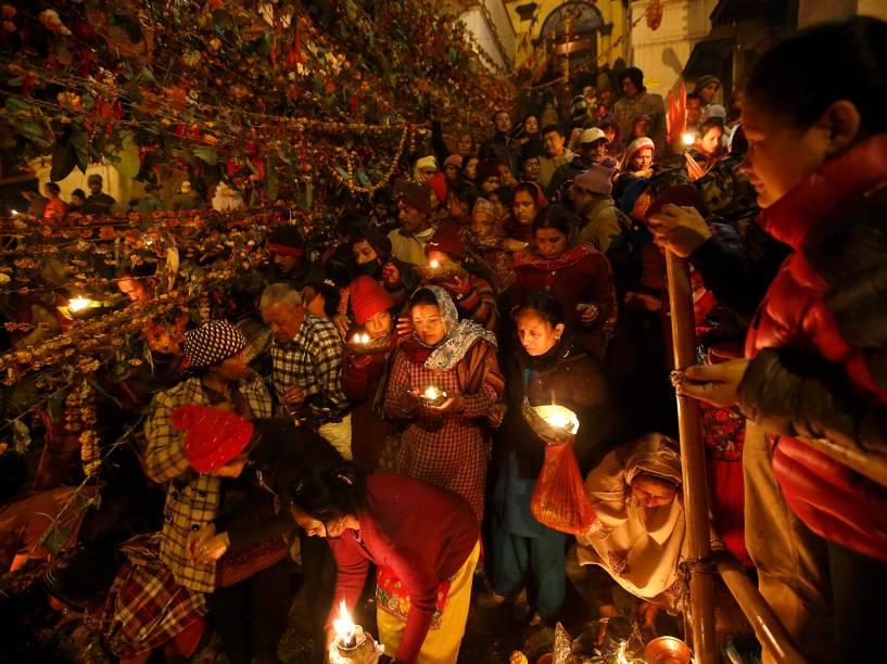 Devotos hindus seguram lâmpadas de óleo durante ritual nas instalações do templo de Pashupatinath, para celebrar o Festival Bala Chaturdashi, em Katmandu, no Nepal