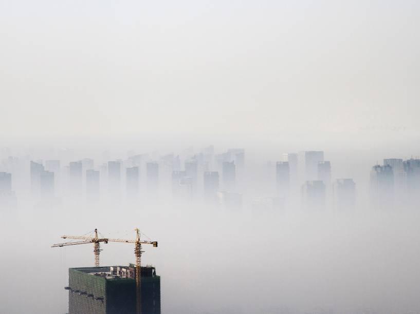 Edifício em construção é visto em meio a uma densa nuvem de poluição em Shenyang, província de Liaoning, na China - 21/11/2014